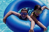 High angle view of a boy and a girl swimming with an inflatable ring in a swimming pool
