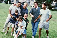Four fathers with their sons playing in a park