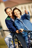 Mature couple standing with bicycles
