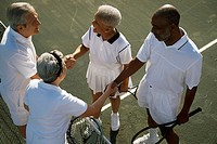 High angle view of two senior couples shaking hands on a tennis court