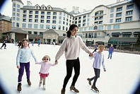 Mother ice skating with her three daughters