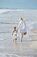 Rear view of a mother and daughter walking on the beach