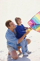 High angle view of a father teaching his daughter to fly a kite