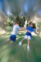 Side profile of a boy and girl swinging on a lawn