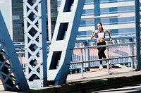 Young woman running on a bridge