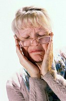 Close-up of a senior woman suffering from a headache