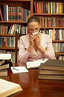 Woman Blowing Nose in Study