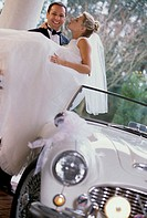 Groom carrying his bride out of a car