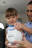 Close-up of a daughter with her mother inserting a coin into a piggy bank
