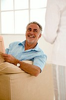Mature couple in living room, man looking at woman, smiling
