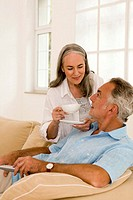 Mature couple in living room, woman holding cup, close-up
