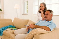 Mature couple in living room, man using remote control
