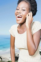Young woman by coast using mobile phone, smiling, portrait