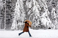 Young woman carrying Christmas gift on shoulders in snow, smiling