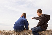 Two boys (11-13) sitting on beach wall, one pointing ahead