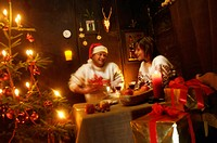 Mid adult couple sitting at table in alpine hut, celebrating Christmas