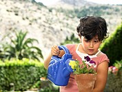 Girl (4-6) watering flower pot in garden