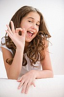Girl (10-12) making OK sign, smiling, portrait, close-up