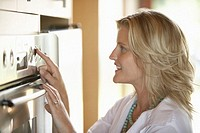 Woman using oven in domestic kitchen, smiling, side view