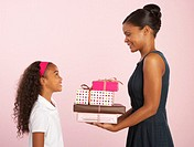 Young woman giving stack of gifts to girl (8-10), smiling, side view