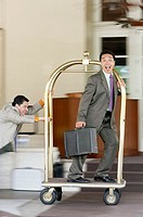 Businessman Riding Luggage Cart