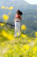 Young woman jogging in meadow, smiling