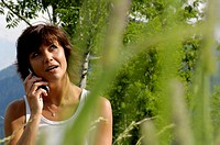 Woman with mobile phone, portrait, outdoors