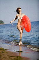 Young woman running on beach, carrying inflatable ring
