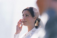 Hispanic woman talking on cellphone outdoors