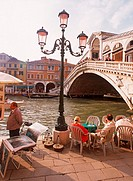 Cafe and tourists on Grand Canal at Rialto Bridge in Venice