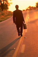 Businessman with briefcase walking endless highway at dawn