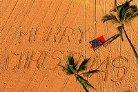 Merry Christmas written on sandy beach in Hawaii