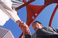 Businessman and woman shaking hands under modern sculpture in downtown Los Angeles