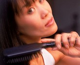 Close up of Asian woman brushing long black hair