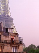 Couple on aptartment balcony under umbrella near Eiffel Tower in Paris