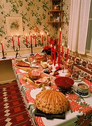 Swedish Christmas table or julbord with chese, baked bread, beer, aquavit, roast ham, marinated herring and candles