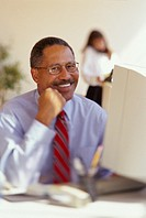 Male African-American executive sitting at his desk and smiling