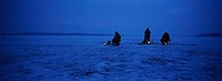 Men ice fishing around lanterns at dawn on frozen lake, St  Paul, MN