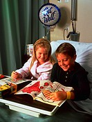 A young girl with blonde hair and a young boy with brown hair smiling while sitting in a hospital bed drawing in a coloring book with a get well ballo...