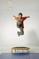 Young boy (8-9) jumping on small trampoline doing karate kick