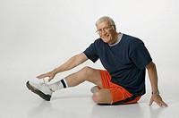 Senior man stretching in studio, portrait
