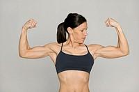 Woman flexing biceps in studio