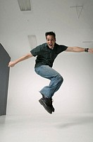 Young man jumping in studio