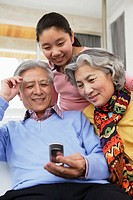 Granddaughter and Grandparents Using Cell Phone