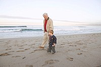Grandfather and Boy Strolling on Beach