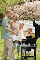 Family Having Barbecue in Garden