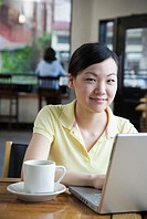 Young Woman Using Laptop in Coffee Shop