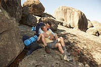 Young Affectionate Couple Resting in Shade During Hiking Trip (thumbnail)