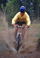 Man wearing helmet and riding mountain bike through muddy stream and splashing water.
