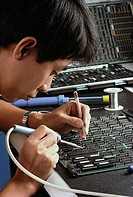 Vietnamese worker repairs circuit board at Filenet in Costa Mesa, CA (released). - BC 2737